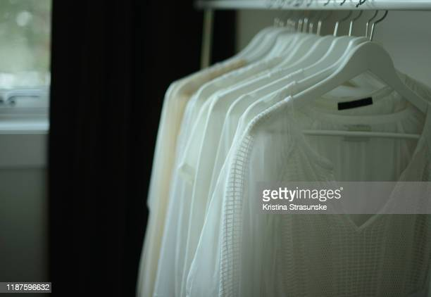 white blouses hanging on a clothing rack - kristina strasunske stock pictures, royalty-free photos & images
