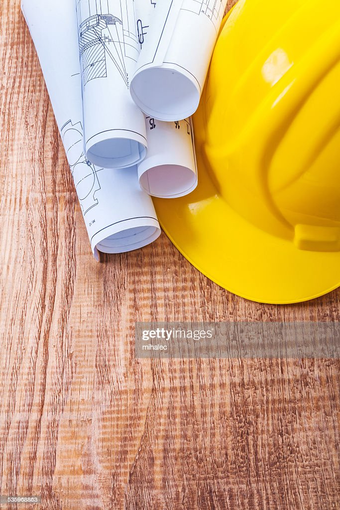 white blueprints and yellow helmet on wooden board : Stock Photo