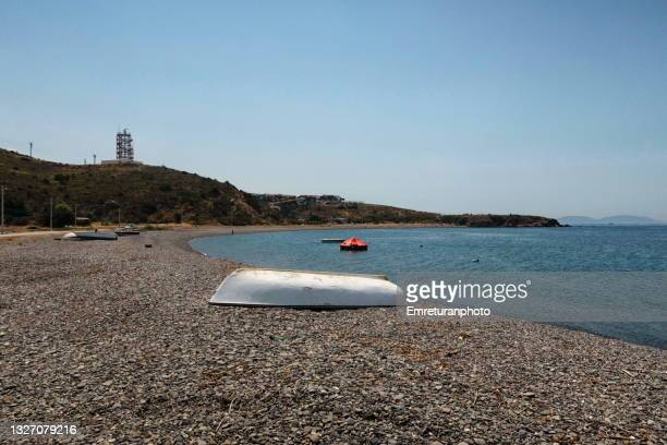 white boat on güzelbahçe pebble beach in aegean turkey. - emreturanphoto stock pictures, royalty-free photos & images