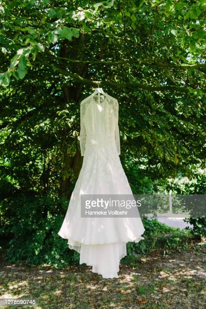 white bohemian wedding dress hanging outside - dress stock pictures, royalty-free photos & images