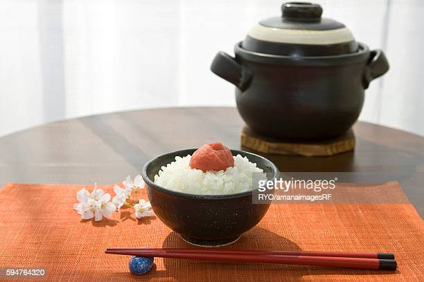 White boiled rice and pickled plum with chopsticks