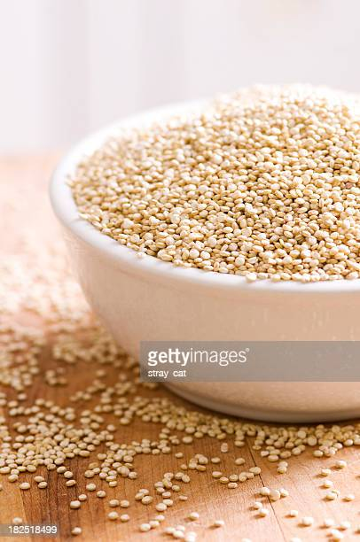White Bowl of raw quinoa on a wood table with spilled grains
