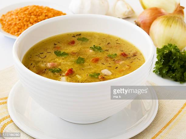 White bowl of vegetable soup with sides