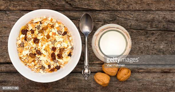 White bowl with Granola or Muesli and a jar of milk or plain yogurt with a spoon on a vintage wood background. Healthy breakfast top view composition with copy space