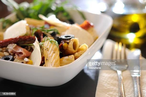 White bowl with pasta dinner, salad and fork