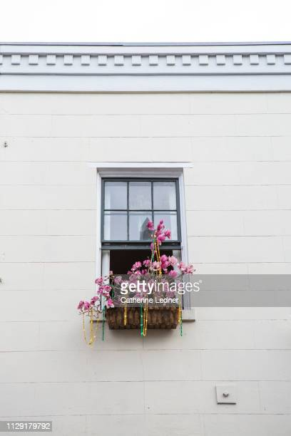 White brick facade with one centered window with fake flowers in window box