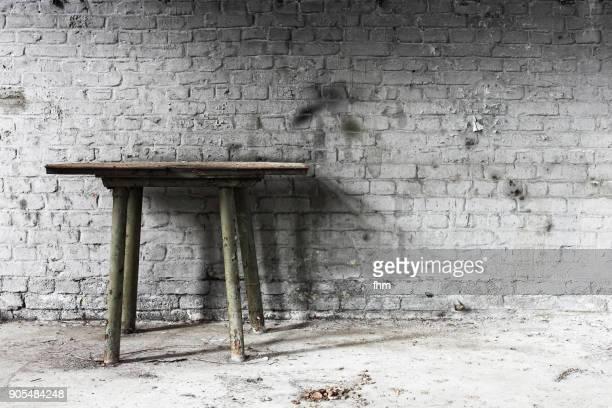 white brick wall in an abandoned builing with old desk - ruina antigua fotografías e imágenes de stock