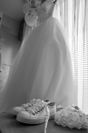 white bridal dress hangs freely on a window and white sneakers ready for the wedding day. accessories for the bride. 996154418