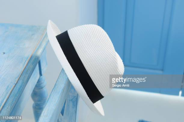 White brimmed straw hat on blue chair