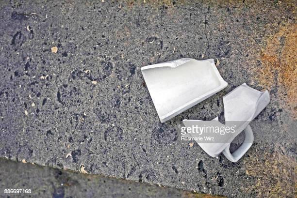 White broken china cup one stone pavement.