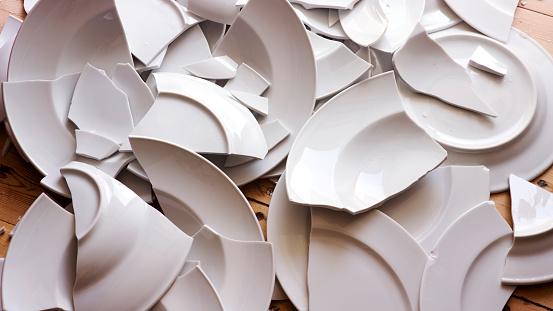 white broken plates on a wooden floor 836292448