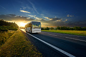 White bus arriving on the asphalt road in rural landscape in the rays of the sunset