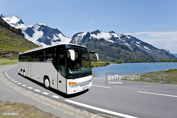 white bus crossing the alpes - coach stock pictures, royalty-free photos & images