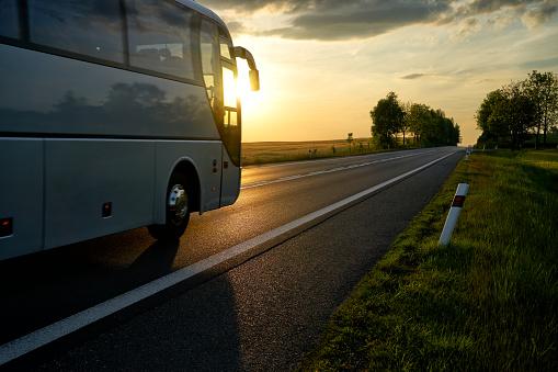 White Bus driving along the asphalt road at sunset. 614316294