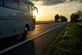 White Bus driving along the asphalt road at sunset.
