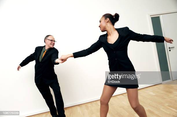 White Businessman and African American Businesswoman Dancing
