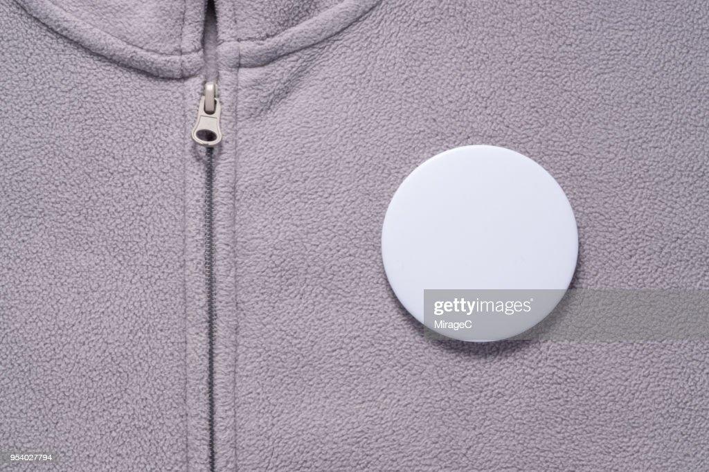 White Button Badge on Gray Cloth : Stock Photo