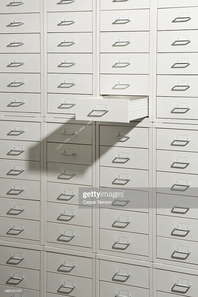 A white cabinet of drawers with one drawer open : Stock Photo