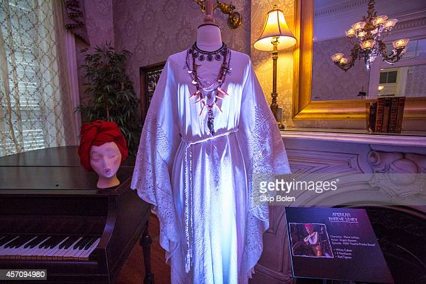 White caftan and 5 necklaces worn by Angela Bassett as 'Marie LaVeau' in 'American Horror Story Coven' to celebrate the October 7 Bluray and DVD...