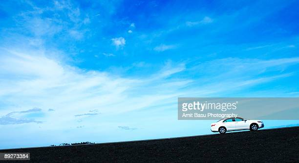 White car going uphill against a bright blue sky