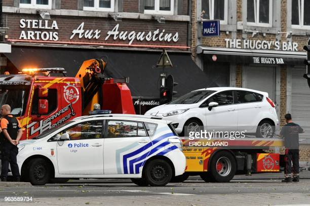 A white car is taken by a tow truck at the scene of a shooting at the boulevard d'Avroy in Liege on May 29 after a gunman killed two female police...