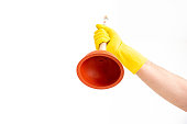 White Caucasian male hand with yellow latex glove holding a sink plunger against white background