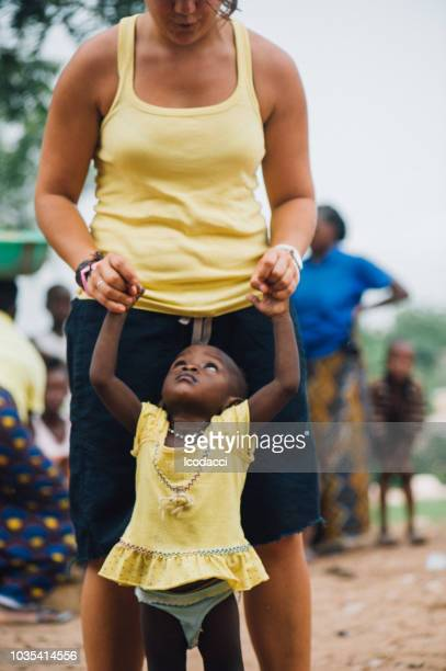 White caucasian young woman plays with black african people in a rural village