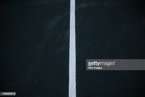 White center line on a black asphalt surface.