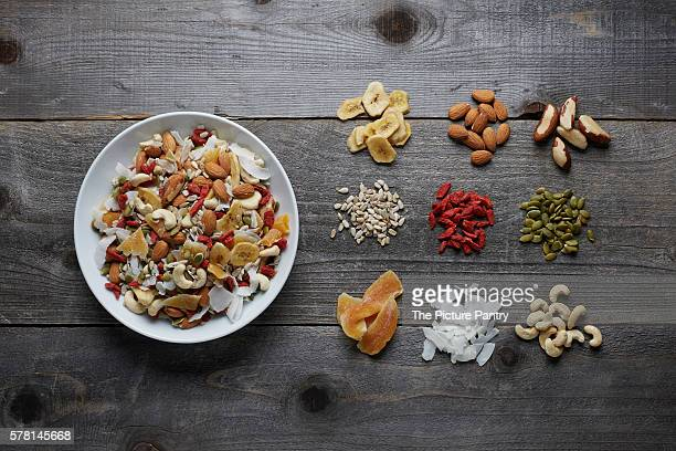 White ceramic bowl full with a healthy trail mix of dried fruits, nuts and seeds