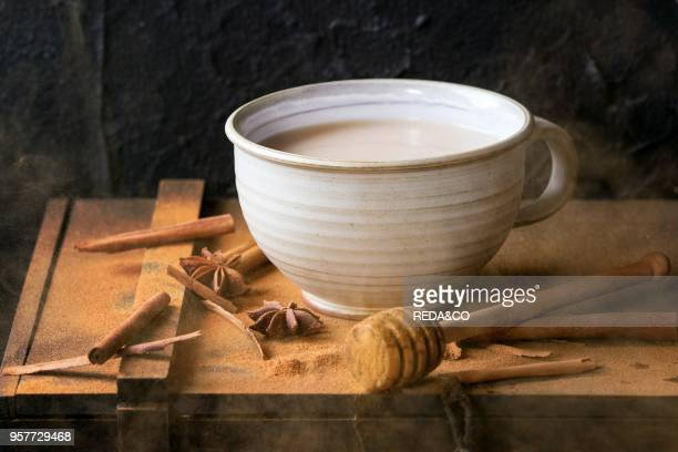 White ceramic cup of hot masala chai served with honey on honey dipper anise cinnamon sticks and powder over black wooden box over black textured...
