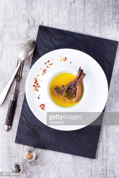 White ceramic plate with well done grilled lamb chop in yellow broth with chili pepper's flackes over black slate board over white wooden table With...