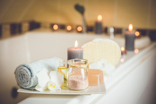 White ceramic tray with home spa supplies in home bathroom for relaxing rituals. Candlelight, salt soap bar, bath salt in jar, massage, bath oil in bottle, blue rolled towel, natural sponge. 1136976095