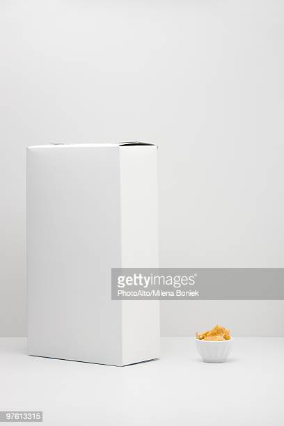 white cereal box and small bowl of cereal - schachtel stock-fotos und bilder