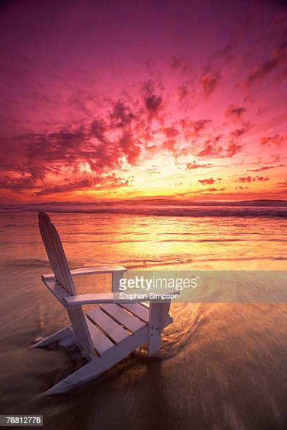 White chair on beach at sunset