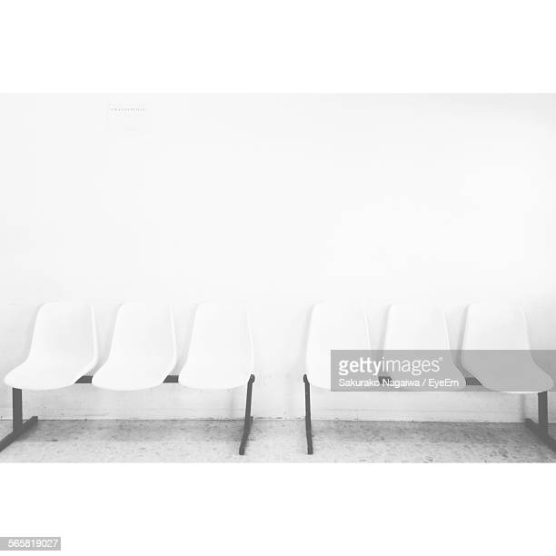 White Chairs Against Wall In Waiting Room
