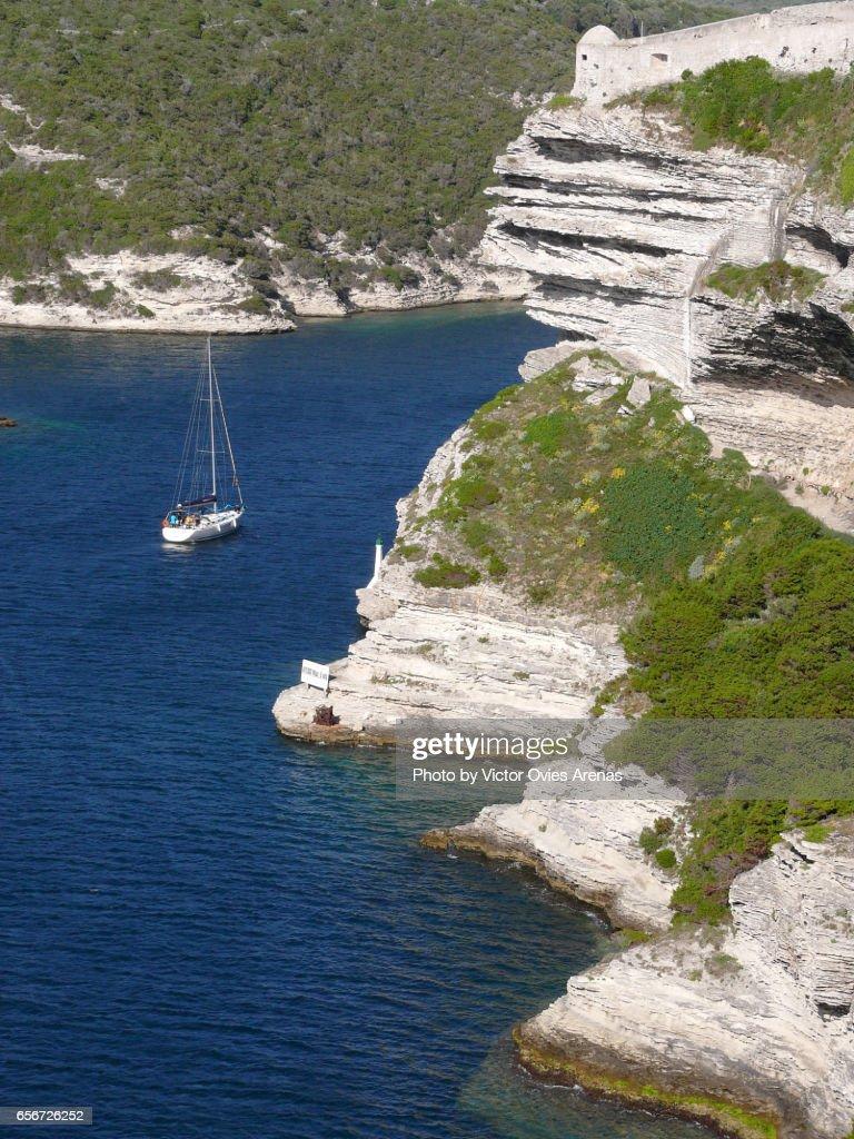 White chalk cliffs of Bonifacio and sail boat entering the harbour in Corsica, France : Foto de stock