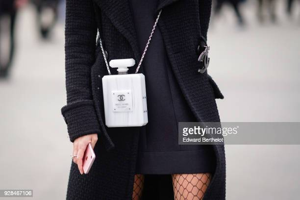 White Chanel bag shaped as a fragrance bottle is seen, outside Chanel, during Paris Fashion Week Womenswear Fall/Winter 2018/2019, on March 6, 2018...