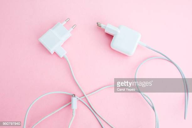 White charging cables for modern smartphone or tablet  in pink background