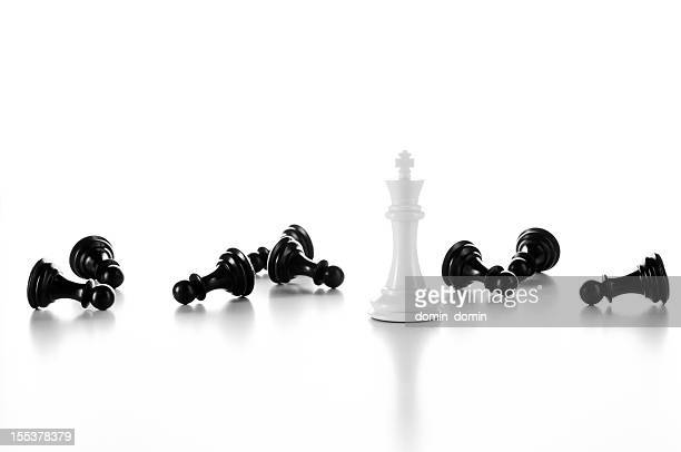 white chess king among lying black pawns, isolated on white - chess piece stock pictures, royalty-free photos & images