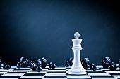 White Chess King among lying down black pawns on chessboard
