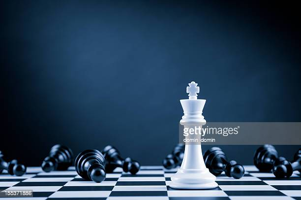 white chess king among lying down black pawns on chessboard - chess stock pictures, royalty-free photos & images