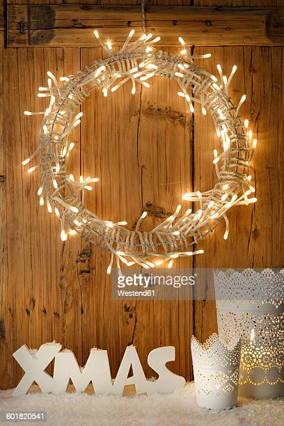 White Christmas decoration with lighted Advent wreath in front of wooden wall
