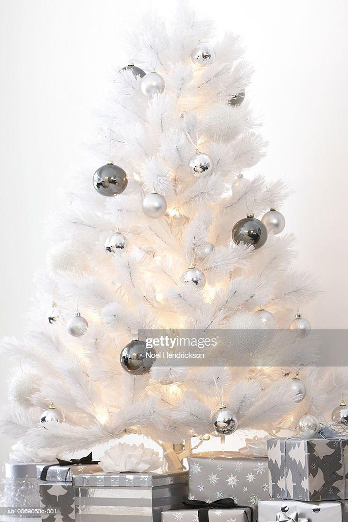 White Christmas tree decorated with silver ornaments and gifts underneath : Stockfoto