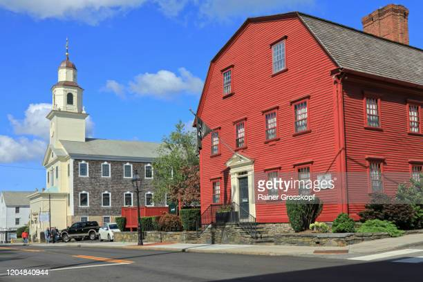 a white church and a red colonial style building against blue sky - rainer grosskopf stock pictures, royalty-free photos & images
