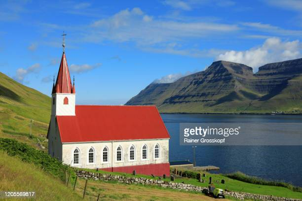 a white church with red roof on the shore of a fjord surrounded by grassy mountains - rainer grosskopf stock pictures, royalty-free photos & images