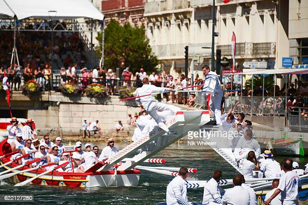 White clad jousters try to push their opponents into the canal during the Languedoc Water Jousting tournament held annually in the port city of Sete in Southern France