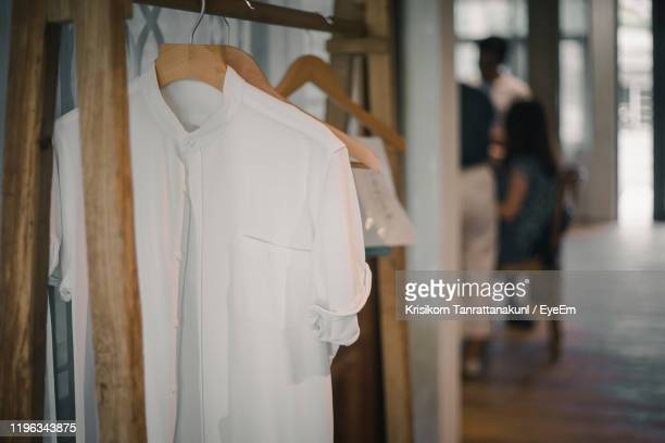 white clothes hanging on door - white shirt stock pictures, royalty-free photos & images