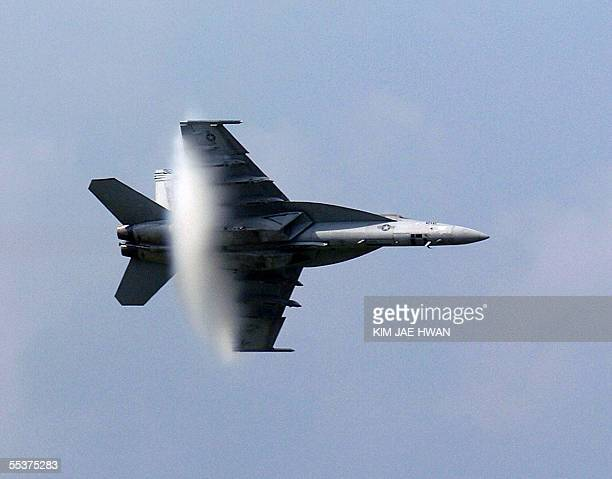 A white cloud forms when a US Navy F/A18E Super Hornet begins flying at a supersonic speed during an air show held in Osan Air Base 55 kilometers...