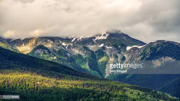 white clouds over forest mountain valley, canada - image stock pictures, royalty-free photos & images