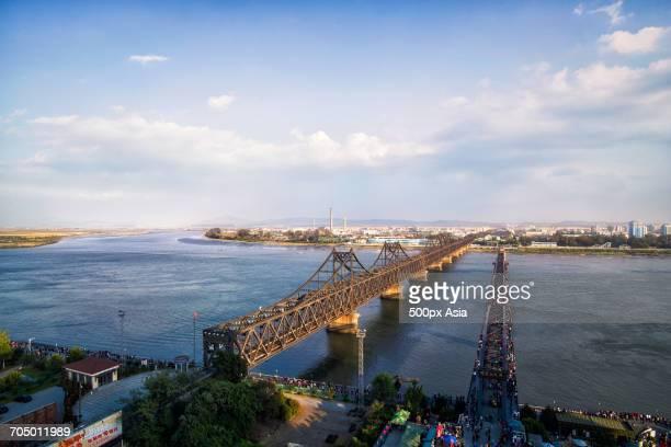 white clouds oversino-korean friendship bridge - yalu river stock pictures, royalty-free photos & images